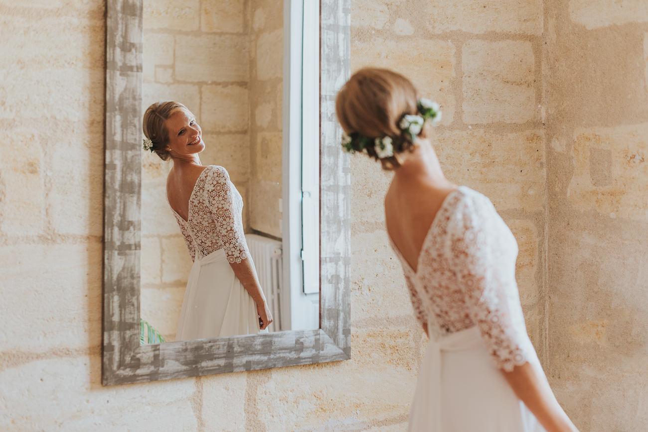 Mariée heureuse qui se regarde dans le miroir