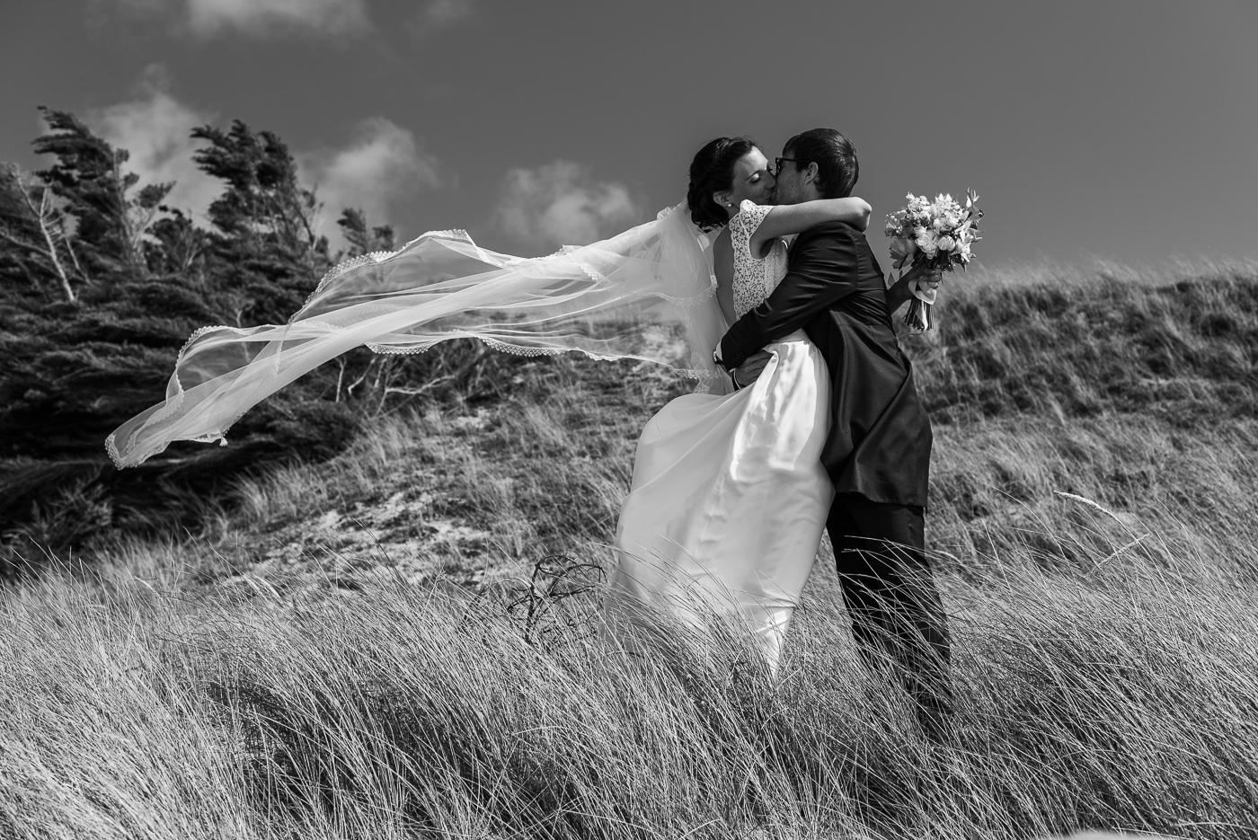 Mariés qui s'embrassent sur la plage
