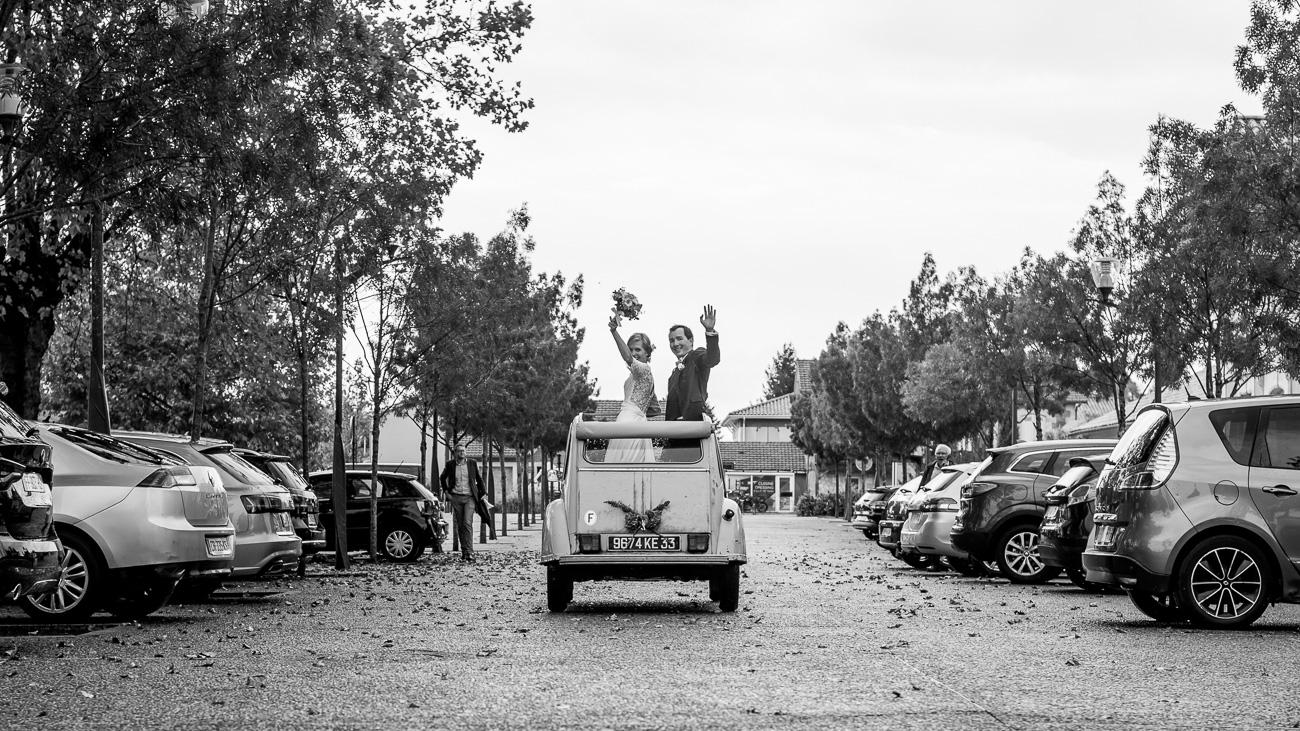Mariés qui partent avec une vieille voiture